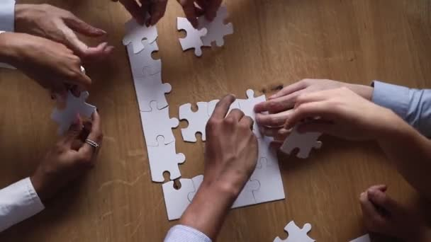 Hands of diverse business team people collaborate assemble puzzle together
