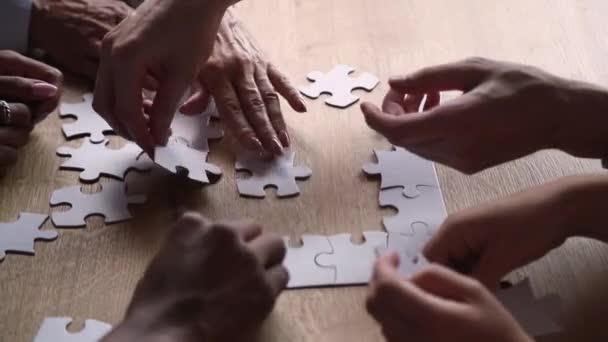 Diverse Hände von Geschäftsleuten verbinden Puzzle auf Schreibtisch