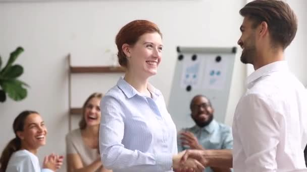 Happy boss handshaking successful female employee expressing gratitude appreciation