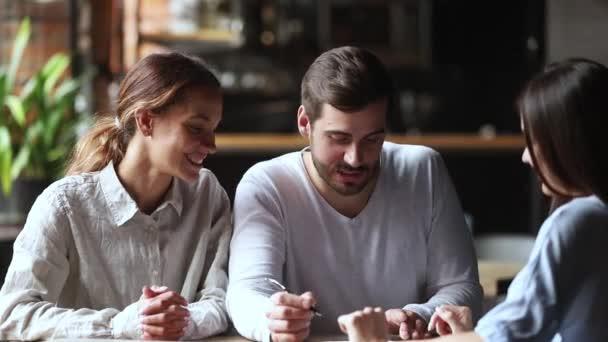 Boldog fiatal pár ügyfelek aláírása biztosítási szerződés kézfogás bróker