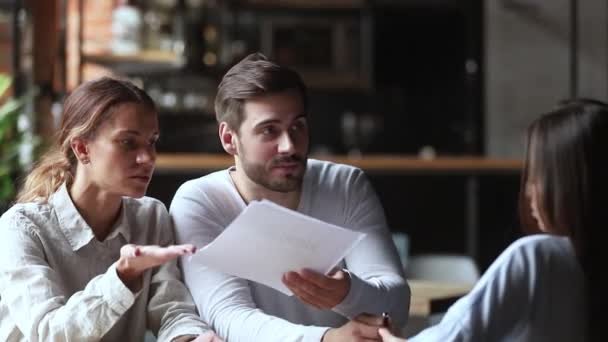 Annoyed angry young couple customers holding papers arguing with manager
