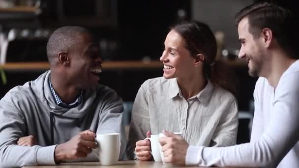 Happy diverse young friends chatting laughing drink tea at meeting