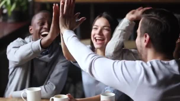 Diverse young happy friends join hands giving high five together