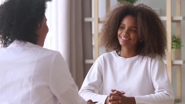 Usmívající se africká americká dospívající dívka naslouchající ženské doktorce
