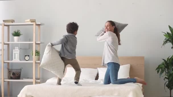 Happy mixed-race mom and son having pillow fight on bed