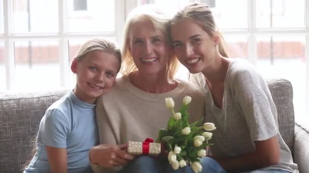 Young mom and little daughter congratulate old grandmother with birthday