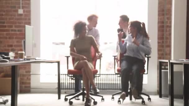 Šťastná multikulturní úřednických smát s fun ježdění na židle