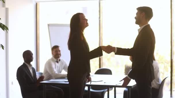 Happy manager handshake promote praise female employee for good work