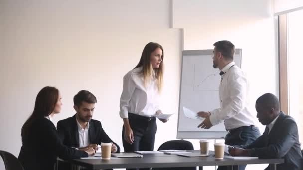 Angry colleagues argue about mistake in papers at office meeting