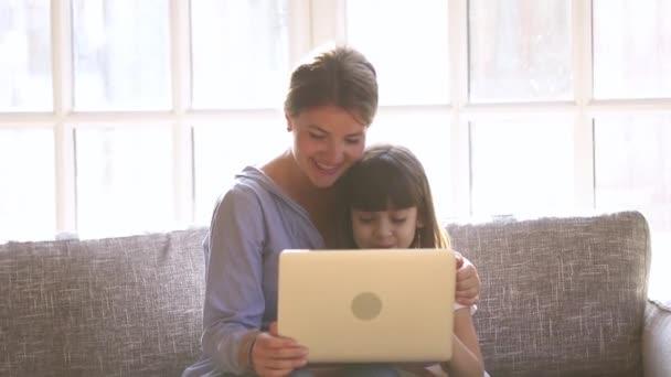 glückliche Mutter mit Kind Tochter hat Spaß mit Laptop
