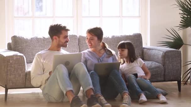 Šťastná moderní rodina sedí na podlaze a mluví pomocí zařízení