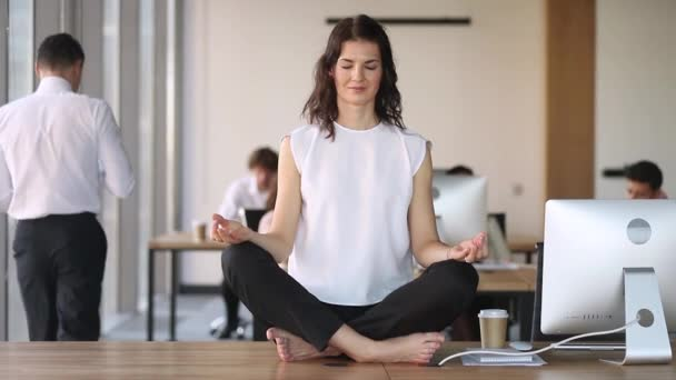 Young calm mindful business woman worker meditate sit on desk