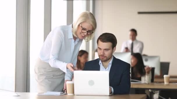 freundliche reife Mentor Coach Führungskraft helfen Mitarbeiter bei der Computerarbeit