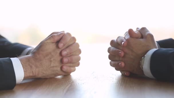 Two businessmen negotiators with clasped male hands negotiate at table