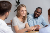Photo Happy smiling young woman talking with coworkers at work