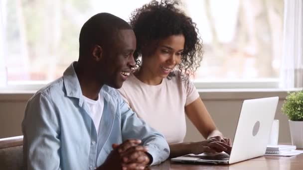 Euphoric african couple looking at laptop excited by online win