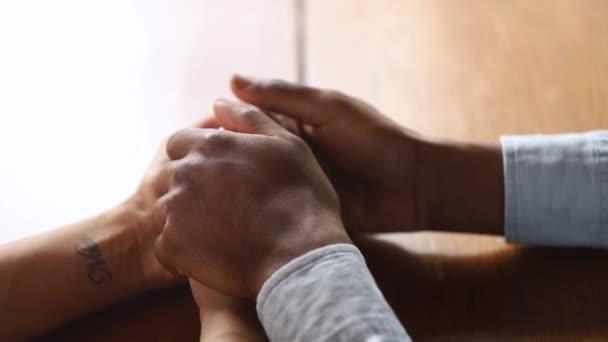 liebevoller afrikanischer Ehemann, der die Hände seiner Frau hält, gibt Halt, Nahaufnahme