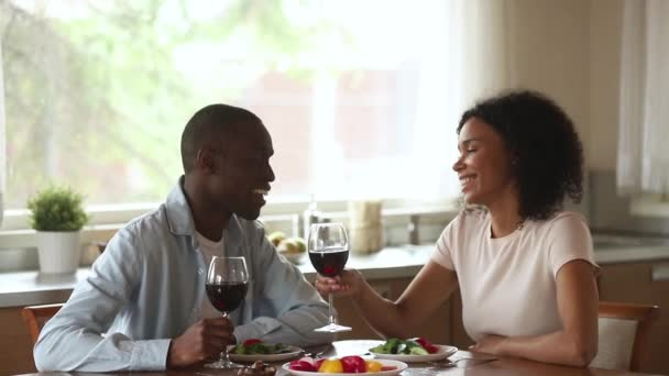 Happy african couple enjoy talking drinking wine sit at table