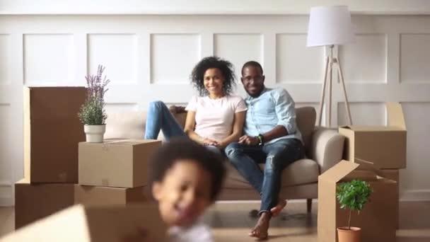 Vzrušené malé africké děti držící krabice v obývacím pokoji