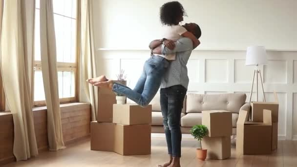 Happy african husband carrying spinning wife celebrate moving day