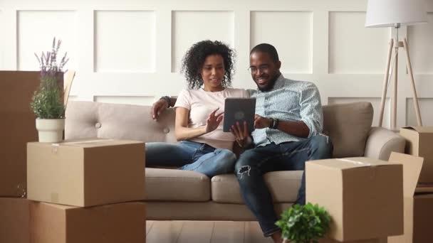 Šťastný africký pár používá digitální tablety v den stěhování
