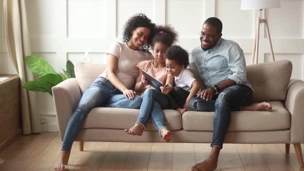 glückliche afrikanische Familieneltern und kleine Kinder mit digitalem Tablet