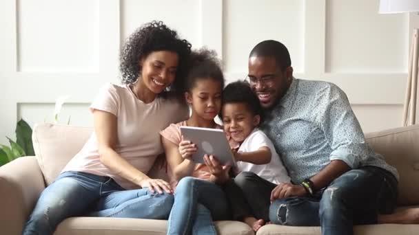 süße afrikanische Kinder spielen mit ihren Eltern ein Spiel mit digitalen Tablets