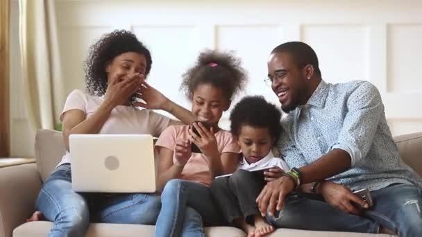 Šťastní afričtí rodiče a děti používající zařízení společně na pohovce