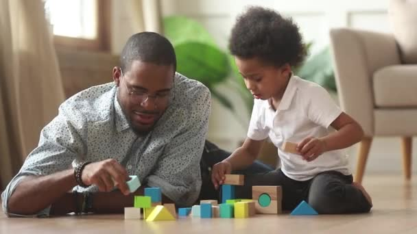 Loving single black father helping little kid son playing together