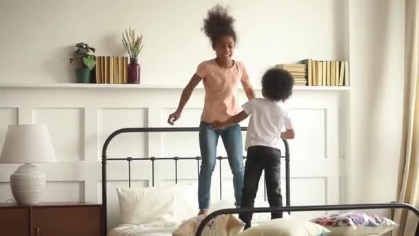 Šťastný malý africký kluk a dívka skáčou po posteli