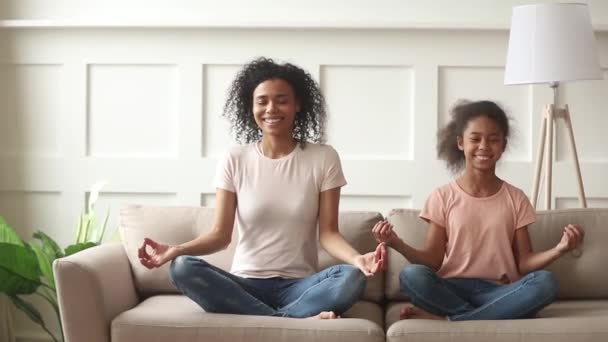 Happy african mom teaching kid daughter doing yoga at home