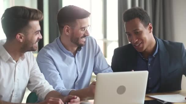 Diverse male business team discussing online startup idea with laptop