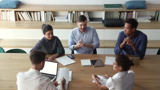 Male boss talking to diverse business people workers at meeting
