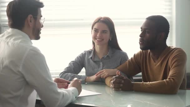 Excited mixed ethnicity couple sign loan contract handshake bank manager