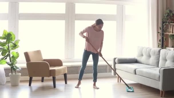 Ordentlich junge Frau Hausfrau sauberen Boden in modernen Wohnzimmer