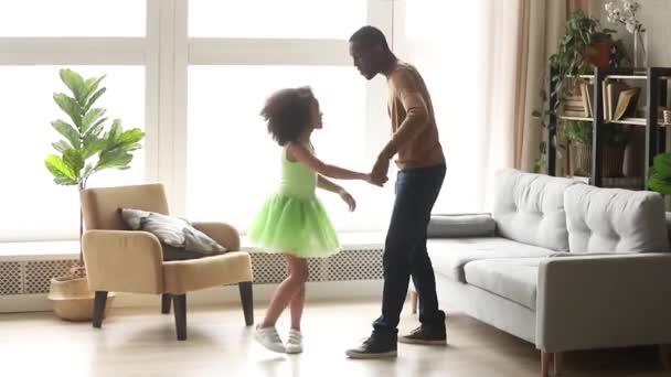 Šťastný africký táta tančí s dcerou dcery v obývacím pokoji