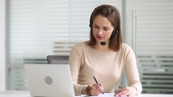 Business woman receptionist wearing headset looking at laptop make notes