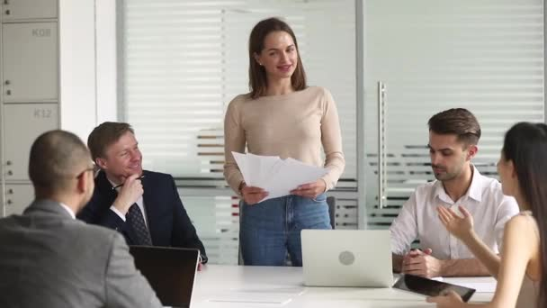 Female manager holding papers talking to employees gathered at meeting