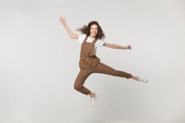 Full length overjoyed young brown-haired woman wearing jumpsuit look at camera jumping feels happy, childish girl having fun, celebrate success achievement moving in studio isolated on grey background stock vector