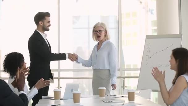 Company staff applauding while director greeting handshakes with new employee