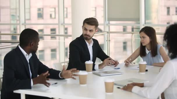 Diverse businesspeople in formal wear negotiating during meeting in boardroom