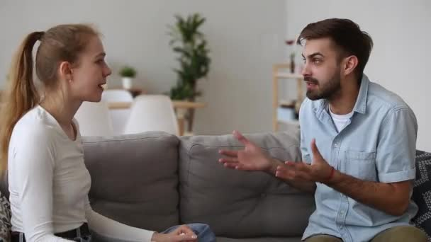 Couple sitting on couch arguing sorting their relationships problems