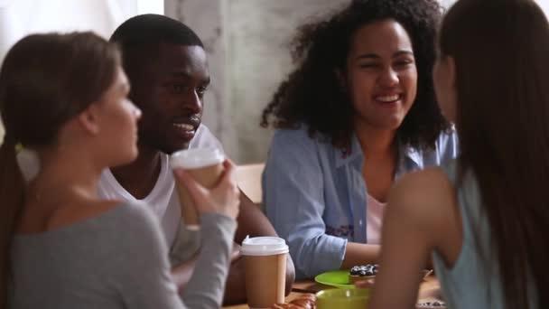 Různorodé studenty, kteří sedí v jídelně a poflakují se spolu