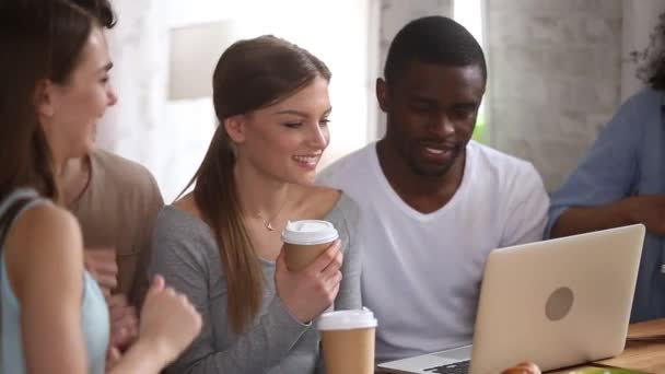 Multiracial friends sitting in cafe using laptop watching comedy movie