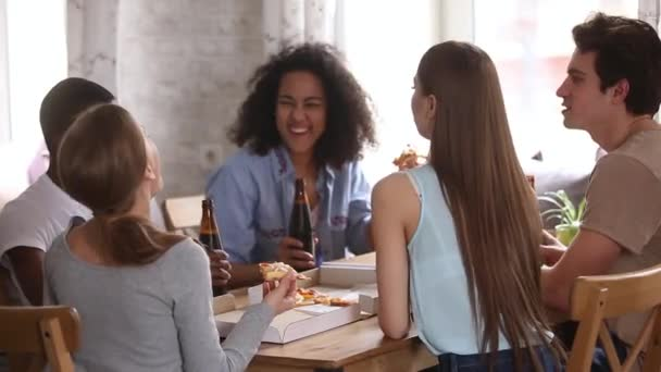 Diverse friends congratulate each other with event clinking beer bottles