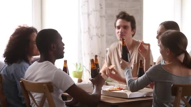 Excited diverse friends hanging out together clinking bottles of beer