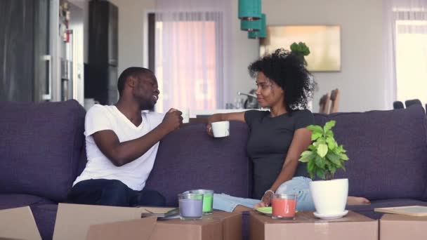 Couple chatting resting on couch drinks tea at new house