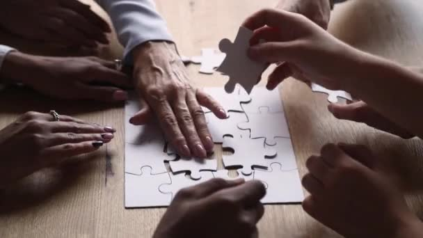 Closeup view multi-ethnic people connecting pieces of puzzle jigsaw