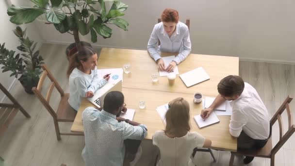 Millennial employees and coach sitting in boardroom view from above