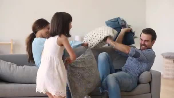 Preschool daughter play with pillow fight with active parents
